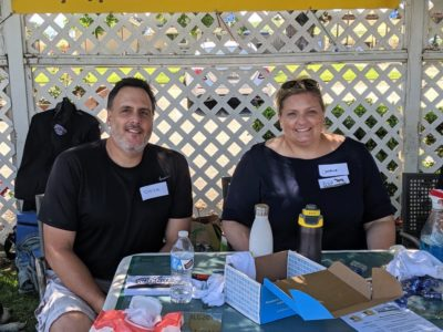 Two volunteers sitting at a table at an event, an example of volunteering