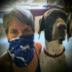 a volunteer wearing the bandana as a face mask, sitting next to her GSP